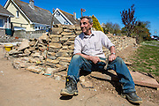 A British stonemason builds a sand-stone wall in the front garden of a home in Wadebridge, Cornwall, UK.