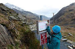 © Licensed to London News Pictures. 30/01/2016. Snowdonia National Park, Gwynedd, Wales, UK. A woman from Snowdonia Warden Services write weather information and warnings at Pen-Y-Pass, at the start of The Pyg Track route up Mount Snowdon. After a mild spell, temperatures dropped to around zero this morning in Snowdonia National Park. A dusting of snow covers the peaks and there is a strong Westerly wind giving a much lower 'feels like' temperature.Photo credit: Graham M. Lawrence/LNP