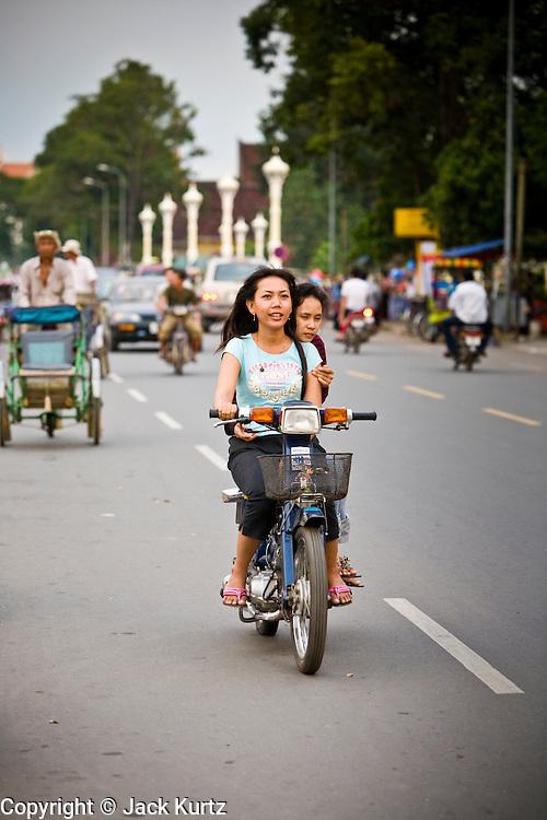 03 JULY 2006 - PHNOM PENH, CAMBODIA: Motorcycle traffic on Sisowath Quay, the main riverfront boulevard in Phnom Penh, Cambodia. Photo by Jack Kurtz