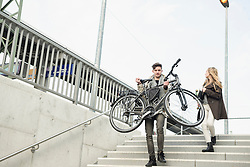 Young man carrying a bicycle and teenage girl holding skateboard  moving down the stairs, Munich, Bavaria, Germany