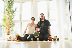 Portrait of happy family with pregnant mother sitting at home