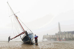 © Licensed to London News Pictures.  20/04/2021. Margate, UK. Father and son paint a boat during warm and foggy afternoon in Margate, east Kent. As a mini heatwave is forecast to hit parts of UK this week with high temperatures reaching 22 celsius. Photo credit: Marcin Nowak/LNP