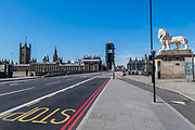 Westminster Bridge is quieter than usual but is still croosed by a small numbe rof people, some in gloves and masks - Anti Coronavirus (Covid 19) outbreak in London.