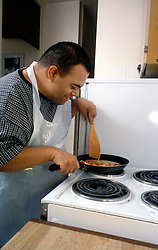 Man with learning difficulty making an omelette in kitchen, UK
