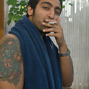 A young Indian guy with a tatoo of the Indian God Shiva on his arm lights two cigarettes at once on a sunday afternoon at the Aqua pool club of the Park Hotel in New Delhi.