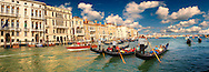 Panoramic of Gondolas on the Grand Canal, Venice, Italy .<br /> <br /> Visit our ITALY HISTORIC PLACES PHOTO COLLECTION for more   photos of Italy to download or buy as prints https://funkystock.photoshelter.com/gallery-collection/2b-Pictures-Images-of-Italy-Photos-of-Italian-Historic-Landmark-Sites/C0000qxA2zGFjd_k . The gondola ( góndoła ) is a traditional, flat-bottomed Venetian rowing boat, well suited to the conditions of the Venetian lagoon.  gondolas are typically propelled by a gondolier, who uses a rowing oar, which is not fastened to the hull, in a sculling manner and also acts as the rudder. The oar of the  gondola rests in an elaborately carved wooden rest (forcola) shaped to project from the side of the craft so as to allow the slight drag of each return stroke to pull the bow back to its forward course. For centuries, the gondola was a major means of transportation and the most common watercraft within Venice. .<br /> <br /> Visit our ITALY HISTORIC PLACES PHOTO COLLECTION for more   photos of Italy to download or buy as prints https://funkystock.photoshelter.com/gallery-collection/2b-Pictures-Images-of-Italy-Photos-of-Italian-Historic-Landmark-Sites/C0000qxA2zGFjd_k