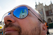 Reflections in a tourists sunglasses of the Church of St Mary on Rynek Glowny market square, on 23rd September 2019, in Krakow, Malopolska, Poland.