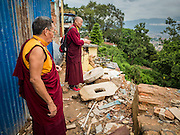 31 JULY 2015 - KATHMANDU, NEPAL: Buddhist monks visit the wreckage of a Buddhist monastery at Swayambhunath, also known as the Monkey Temple. Two monks were killed when the monastery was destroyed by the earthquake. Swayambhunath is a complex of Buddhist and Hindu temples in Kathmandu. It was heavily damaged in the Nepal Earthquake. The Nepal Earthquake on April 25, 2015, (also known as the Gorkha earthquake) killed more than 9,000 people and injured more than 23,000. It had a magnitude of 7.8. The epicenter was east of the district of Lamjung, and its hypocenter was at a depth of approximately 15 km (9.3 mi). It was the worst natural disaster to strike Nepal since the 1934 Nepal–Bihar earthquake. The earthquake triggered an avalanche on Mount Everest, killing at least 19. The earthquake also set off an avalanche in the Langtang valley, where 250 people were reported missing. Hundreds of thousands of people were made homeless with entire villages flattened across many districts of the country. Centuries-old buildings were destroyed at UNESCO World Heritage sites in the Kathmandu Valley, including some at the Kathmandu Durbar Square, the Patan Durbar Squar, the Bhaktapur Durbar Square, the Changu Narayan Temple and the Swayambhunath Stupa. Geophysicists and other experts had warned for decades that Nepal was vulnerable to a deadly earthquake, particularly because of its geology, urbanization, and architecture.        PHOTO BY JACK KURTZ