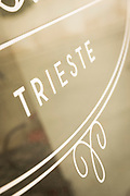 Close-up of coffee shop window with white inscription, Trieste, Italy