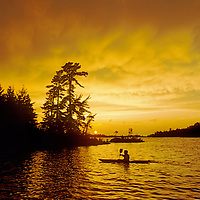 A kayaker paddles after a clearing storm on Lake of the Woods, Ontario, Canada.  Jay Jensen (MR).