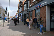 Local response to Coronavirus is felt on a street by street level as People wearing face masks go about their day to day banking, seen here queueing outside Nationwide Building society on Kings Heath High Street on 6th April 2020 in Birmingham, England, United Kingdom. Coronavirus or Covid-19 is a new respiratory illness that has not previously been seen in humans. While much or Europe has been placed into lockdown, the UK government has announced more stringent rules as part of their long term strategy, and in particular social distancing.