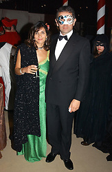 ROWAN ATKINSON and his wife SUNETRA at the 2004 Goodwood Revival ball this year theme was a Venetian Masked Ball, held at Goodwood Motor Racing circuit, West Sussex on 4t September 2004.