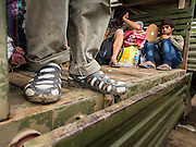 16 JUNE 2014 - POIPET, CAMBODIA: Cambodian migrants sit in the back of a Cambodian Army truck in Poipet waiting to be taken back to their homes. More than 150,000 Cambodian migrant workers and their families have left Thailand since June 12. The exodus started when rumors circulated in the Cambodian migrant community that the Thai junta was going to crack down on undocumented workers. About 40,000 Cambodians were expected to return to Cambodia today. The mass exodus has stressed resources on both sides of the Thai/Cambodian border. The Cambodian town of Poipet has been over run with returning migrants. On the Thai side, in Aranyaprathet, the bus and train station has been flooded with Cambodians taking all of their possessions back to Cambodia.   PHOTO BY JACK KURTZ