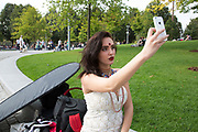 Asian model has her make up done my a make up artist prior to a photo shoot at Jubilee Gardens. Here she take a selfie of herself to post on social media. The South Bank is a significant arts and entertainment district, and home to an endless list of activities for Londoners, visitors and tourists alike.