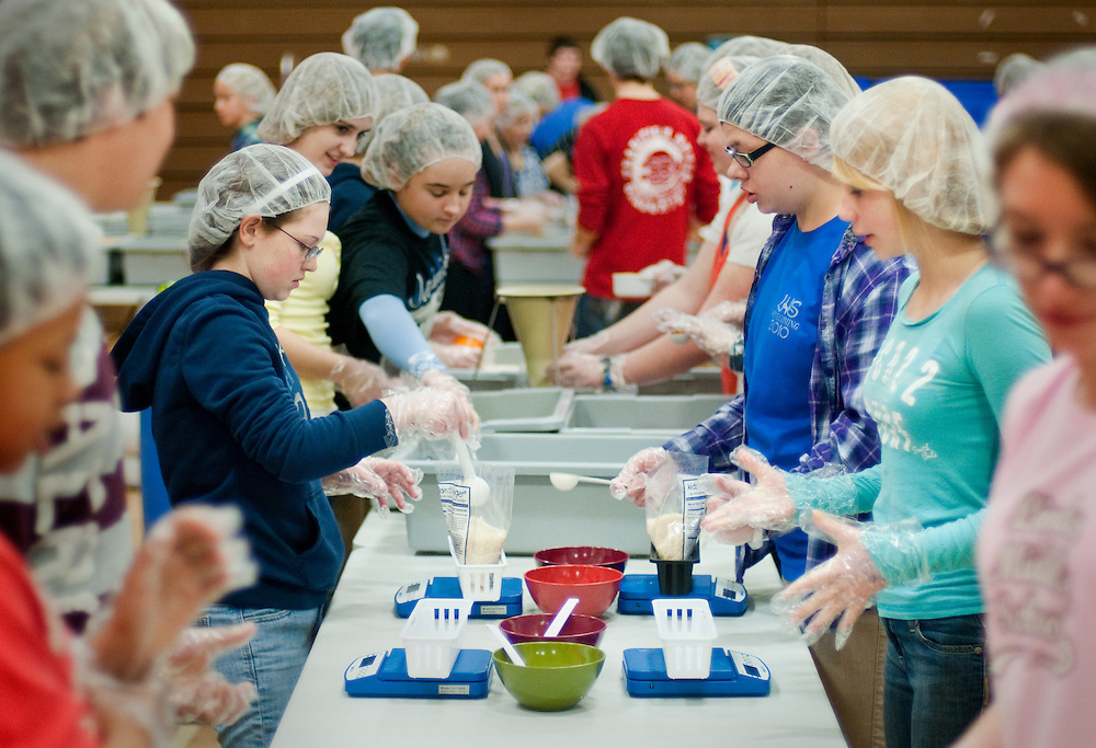 Matt Dixon | The Flint Journal..Students from Linden High School and middle schools participate in Kids Against Hunger in the high school's gym by packaging meals. About 80 students packed over 10,000 bags of food with rice, soy, dried vegetables and dried chicken. About a third of the bags will go to local food banks and the rest will be used to feed families in other countries and disaster relief programs.