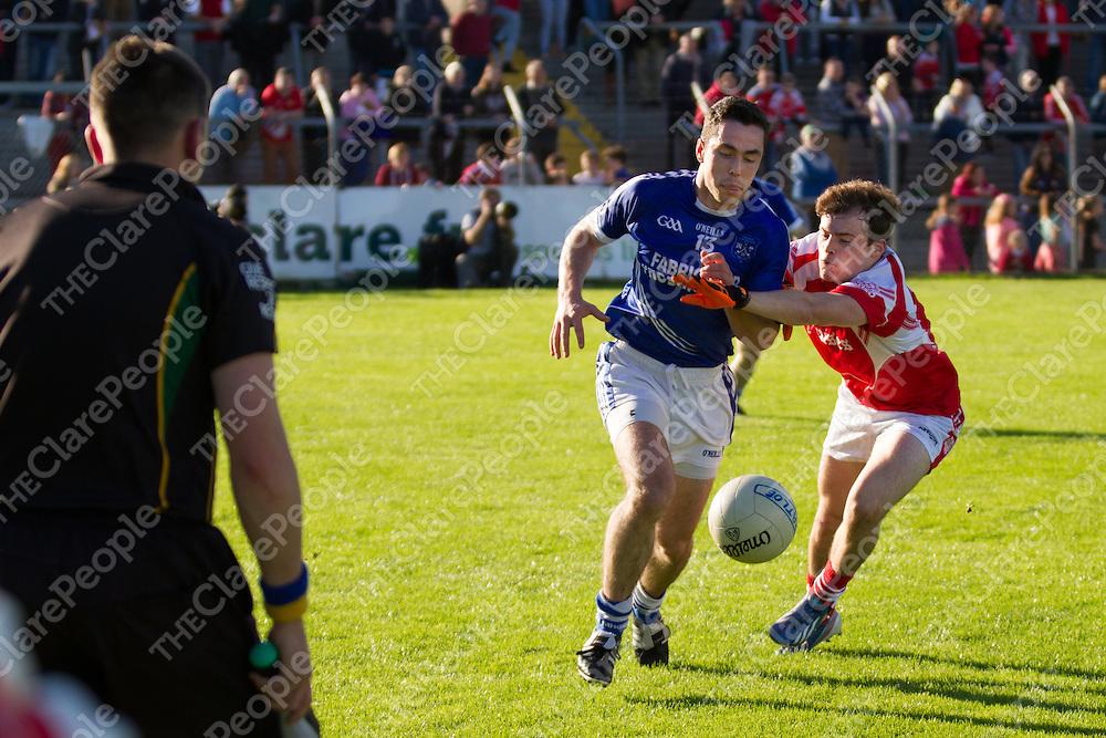 Cratloe's Conor McGrath pulled back by Éire Óg's Eimhin Courtney