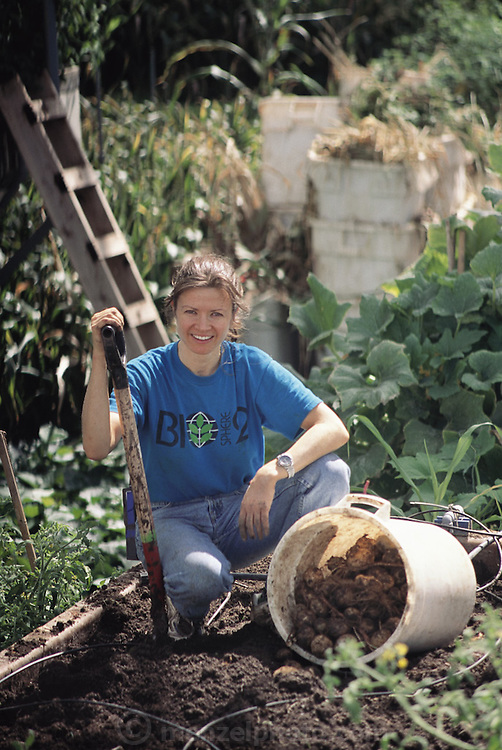 USA_SCI_BIOSPH_69_xs <br /> Biosphere 2 Project undertaken by Space Biosphere Ventures, a private ecological research firm funded by Edward P. Bass of Texas.  'Biospherian' Jayne Poynter harvesting potatoes inside Biosphere 2 in the intensive agriculture biome.  Biosphere 2 was a privately funded experiment, designed to investigate the way in which humans interact with a small self-sufficient ecological environment, and to look at possibilities for future planetary colonization. The $30 million Biosphere covers 2.5 acres near Tucson, Arizona, and was entirely self- contained. The eight 'Biospherian's' shared their air- and water-tight world with 3,800 species of plant and animal life. The project had problems with oxygen levels and food supply, and has been criticized over its scientific validity. 1992