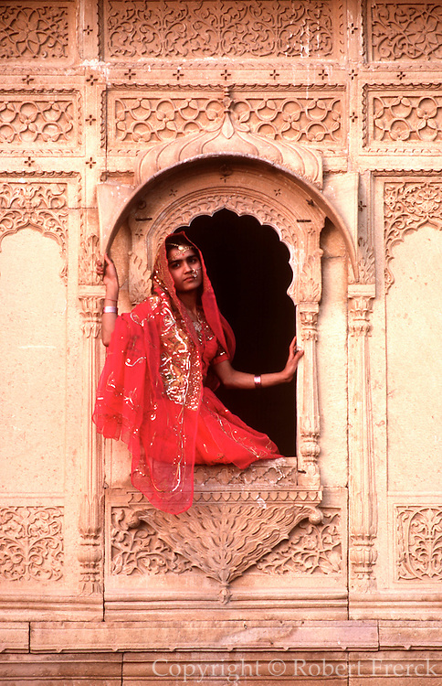 INDIA, PORTRAITS a young woman sitting in the window of a  'Hivelis' or palace in the historic city  of Jaisalmer in the Great Thar Desert