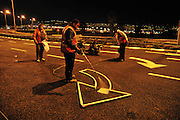 Workers paint road markings at night