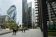 Angled view of the cityscape and skyline reflections looking towards 1 St Mary Axe aka the Gherkin as people in small numbers interact in the quiet urban landscape on 26th May 2021 in London, United Kingdom. As the coronavirus lockdown continues its process of easing restrictions, the City remains far quieter than usual, which asks the question if normal numbers of people and city workers will ever return to the Square Mile.