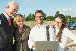 Four smiling people with laptop outdoors