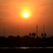 The setting sun over the Mekong River in Vientiane, Laos. Because the river marks the border, the trees and towers that are silhouetted on the far bank of the river are in Thailand.