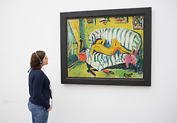 Woman looking at painting Liegendes Madchen by Erich Heckel at Pinakothek Moderne art museum in Munich Germany