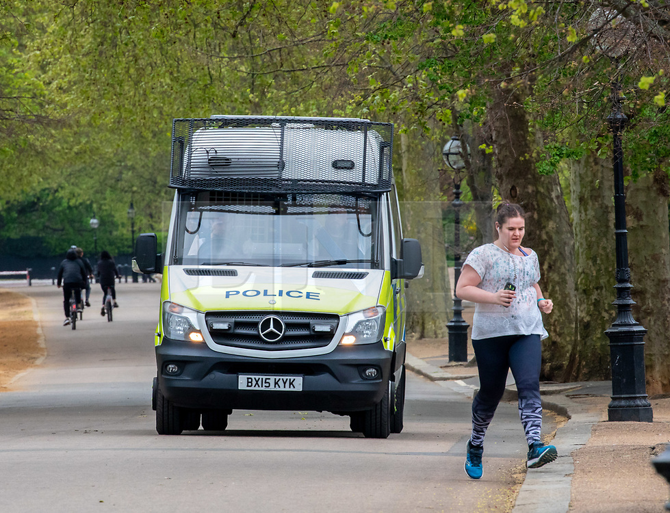 © Licensed to London News Pictures. 17/04/2020. London, UK. A Police van patrols Hyde Park as members of the public exercise. Police continue to patrol the parks enforcing lockdown rules on social distancing and exercise. Photo credit: Alex Lentati/LNP