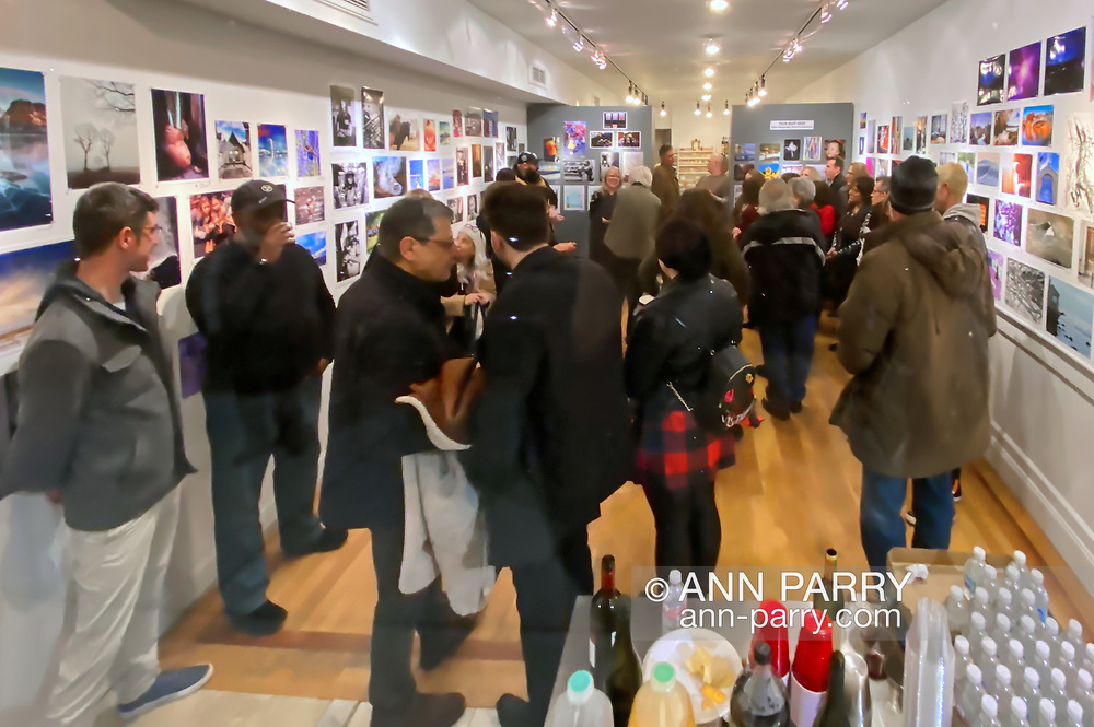 Huntington, New York, U.S. February 29, 2020. Seen through the large front window of fotofoto gallery is the 'Your Best Shot' Reception for its Open Photography push-pin exhibition.