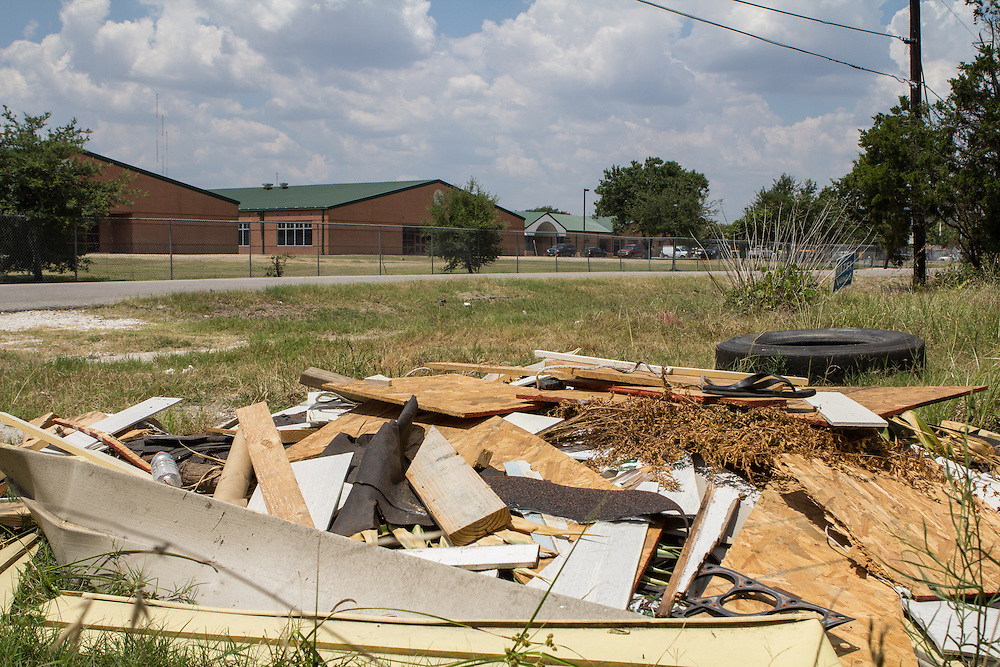 There is a dumping ground across from B.C. Elmore Elementary. Children walking to or from school could suffer injuries from protruding nails, broken glass, etc.