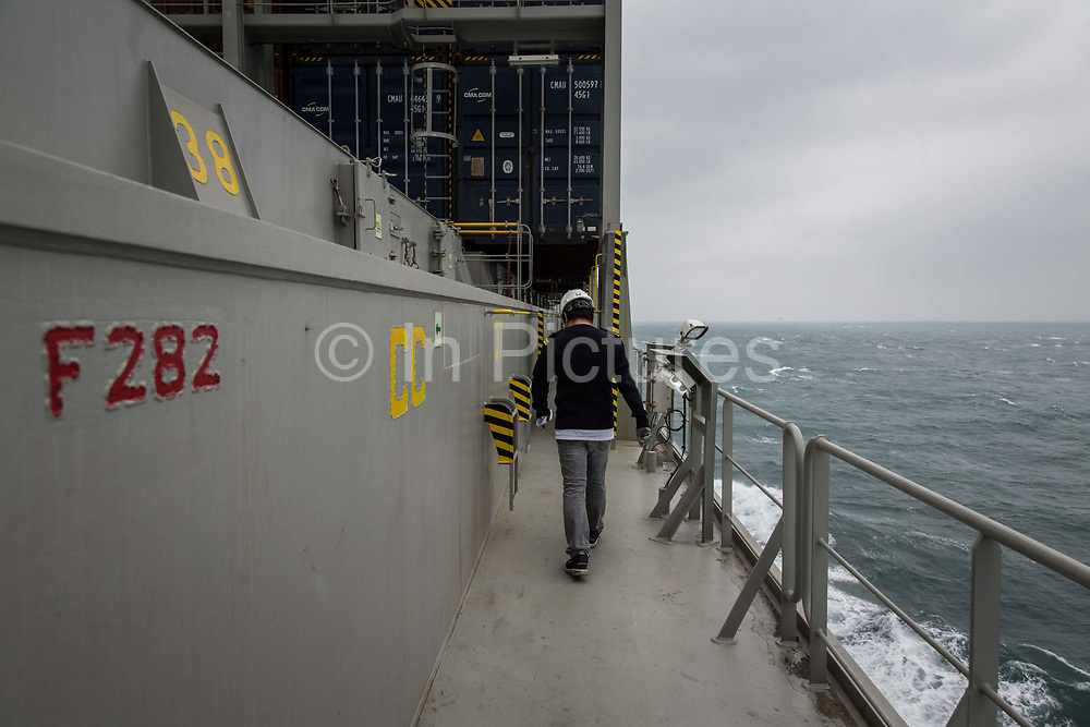 A crew member walks through CMA CGM SAs Benjamin Franklin container ship as it sails off the coast of southern China, on Sunday, Jan. 31, 2016. The Benjamin Franklin is the largest container ship ever to have docked at a U.S. port.