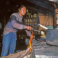 A young Sherpa woman (Sherpani) prepares meals for trekkers in her family's lodge in Namche Bazaar, the leading Sherpa town in Nepal's Himalaya.