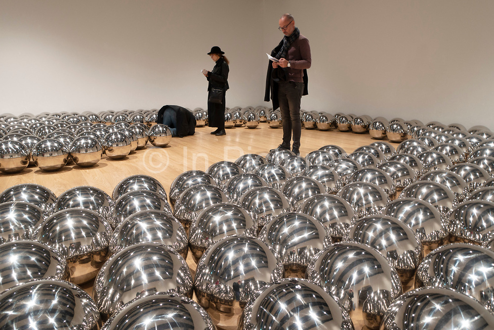 Visitors interacting with artworks at the Space Shifters exhibition at the Hayward Gallery on 16th December 2018 in London, United Kingdom. The exhibit was a major group show of sculptures and installations that explored perception and space, featuring 20 artists. Narcissus Garden 1966–2018 by Yayoi Kusama.