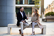 Man and woman sat on a bench together chatting and working from a laptop in the offshore banking and finance area of St Helier, Jersey, CI