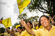 05 DECEMBER 2012 - BANGKOK, THAILAND:  Thai women wave flags on the Royal Plaza Wednesday while they wait to see Bhumibol Adulyadej, the King of Thailand, before his public audience at the Mukkhadej balcony of the Ananta Samakhom Throne Hall. December 5 is a national holiday. It's also celebrated as Father's Day. Celebrations are being held across the country to mark the birthday of Bhumibol Adulyadej, the King of Thailand.   PHOTO BY JACK KURTZ