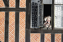 An onlooker is seen watching from a window of a building inside Windsor Castle as guests arrive for the wedding of Princess Eugenie to Jack Brooksbank at St George's Chapel.