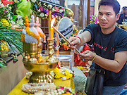28 APRIL 2014 - BANGKOK, THAILAND: A man lights an incense stick for Kamol Duangphasuk, 45, during the funeral for Kamol at Wat Samian Nari in Bangkok. Kamol was a popular poet who wrote under the pen name Mai Nueng Kor Kunthee. Kamol had been writing since the 1980s and was an outspoken critic of the 2006 coup that deposed Thaksin Shinawatra. After the 2010 military crackdown against the Red Shirts he went into temporary self imposed exile fearing for his safety. After he returned to Thailand he organized weekly protests against Thailand's Lese Majeste laws, which he said were being used to stifle dissent. Kamol was shot and murdered on April 23. The assailants are still at large but the murder is thought to be political.     PHOTO BY JACK KURTZ