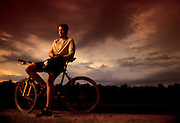 A mountain biker takes a break from a day of riding the trails as the sun sets over a park