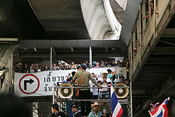 © Licensed to London News Pictures. 05/01/2014. Anti-Government Protesters ride on the back of a truck and are cheered on by protestors from the platform of the Skyrail system during the third day of the 'Bangkok Shutdown' as anti-government protesters continue with their 'shutdown' of Bangkok.  Major intersections in the heart of the city have been blocked in their campaign to oust Prime Minister Yingluck Shinawatra and her government in Bangkok, Thailand. Photo credit : Asanka Brendon Ratnayake/LNP