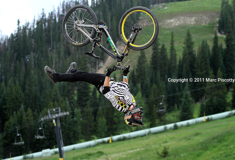 SHOT 7/29/11 2:36:59 PM - Cam McCaul gets inverted off a jump during slopestyle qualifiers at Crankworx Colorado at the Trestle Bike Park in Winter Park, Co. McCaul won the event with a score of 93.00. The event is a Pro-am mountain bike competition featuring a dual slalom race, the Trestle Unchained Challenge, slopestyle and cross country racing events where top pros competed for more than $35,000 in prize money. (Photo by Marc Piscotty / © 2011)