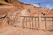 A cattle guard fence spans Halfway Hollow along trail to Zebra Slot Canyon, Grand Staircase Escalante National Monument, Utah, USA. Directions to unmarked trailhead for Zebra and Tunnel Slot Canyons: From Escalante town, drive 6 miles east on Highway 12, turn right on Hole-in-the-Rock Road, drive 7.8 miles to the third cattle guard and park on west side of road. Hike east on well-trodden but unmarked path, 5 miles round trip to Zebra Slot, plus an optional 3 miles round trip to Tunnel Slot (750 feet gain over 8 miles), using map from GSENM Visitor Center or canyoneeringusa.com.