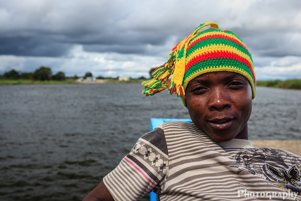 Portrait of young African boy with knit hat in boat on the river in the Okavango Panhandle, Botswana, Africa