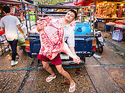 13 FEBRUARY 2014 - BANGKOK, THAILAND:   A man delivers sides of pig to a meat stall in Klong Toei Market in Bangkok. Khlong Toei is the largest wet market in Bangkok.   PHOTO BY JACK KURTZ