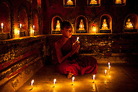 Prayer of a young Buddhist monk in a candle-light temple, Myanmar. Exotic places fine art photography prints.