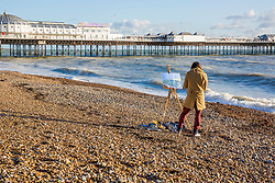 © Licensed to London News Pictures. 25/11/2017. Brighton, UK. An artist paints on the beach in Brighton and Hove as Brighton and Hove beach and the Palace Pier basks in sunshine. Photo credit: Hugo Michiels/LNP
