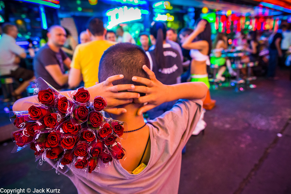 """19 JANUARY 2013 - BANGKOK, THAILAND:  A child tries to sell roses to tourists on Soi Cowboy, a red light district in Bangkok. Prostitution in Thailand is technically illegal, although in practice it is tolerated and partly regulated. Prostitution is practiced openly throughout the country. The number of prostitutes is difficult to determine, estimates vary widely. Since the Vietnam War, Thailand has gained international notoriety among travelers from many countries as a sex tourism destination. One estimate published in 2003 placed the trade at US$ 4.3 billion per year or about three percent of the Thai economy. It has been suggested that at least 10% of tourist dollars may be spent on the sex trade. According to a 2001 report by the World Health Organisation: """"There are between 150,000 and 200,000 sex workers (in Thailand).""""       PHOTO BY JACK KURTZ"""