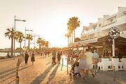 Pedestrians walking on sidewalk at sunset, Paphos, Cyprus