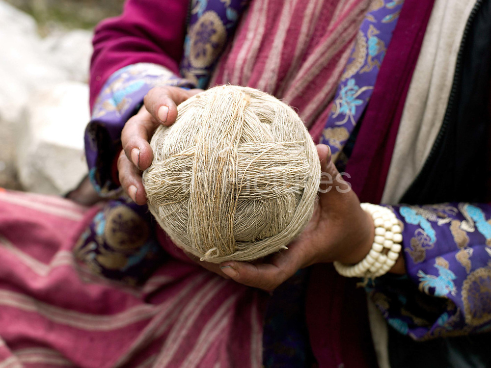 A Brokpa woman holds a ball of sheep wool which was spun using a drop spindle called a Yoekpa, Merak, Eastern Bhutan. The Brokpa, the semi-nomads of the villages of Merak and Sakteng are said to have migrated to Bhutan a few centuries ago from the Tshona region of Southern Tibet. Thriving on rearing yaks and sheep, the Brokpas have maintained many of their unique traditions and customs. Given the geographic isolation of many of Bhutan's villages, there are 16 different dialects and 14 regional groups in the country. Many tribes have kept alive their distinct cultural identities through their dress, language and traditions over the years.