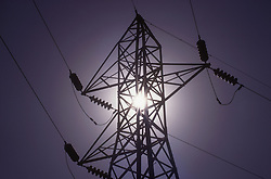 Electricity pylon in India with the sun seen behind it giving a glow and flashes of light,