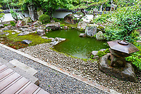 """Saikyoji Garden - altogether there are four distinct gardens surrounding the temple's main hall.  The most famous one is the Hyakuden Teien pond garden designed by Kobori Enshu during the Ido Period,  The pond is supposed to represent Lake Biwa nearby (others contend that the pond is in the shape of a rose)  with its backdrop slope punctuated with stones and satsuki bushes.  Adjacent to the pond is a sukiya style teahouse, an addition added during the Meiji Period that is almost never open to the public.   The second garden is called Dai Honbo Teien - its style is quite different from the Hyakuden Garden as it is composed of bushes in the tsukiyama style - its unique feature is of stepping stones embedded in the white sand """"sea"""". The third garden is the Shoin Teien, which is a dry garden created during the Meiji Period, and is composed of Sakamoto style masonry and stones.  The fourth main garden is Yashoiun Teien or Back Shoin Garden which was created much more recently by Shigetaro Nishimura a local landscaper and is considered a pond appreciation garden."""